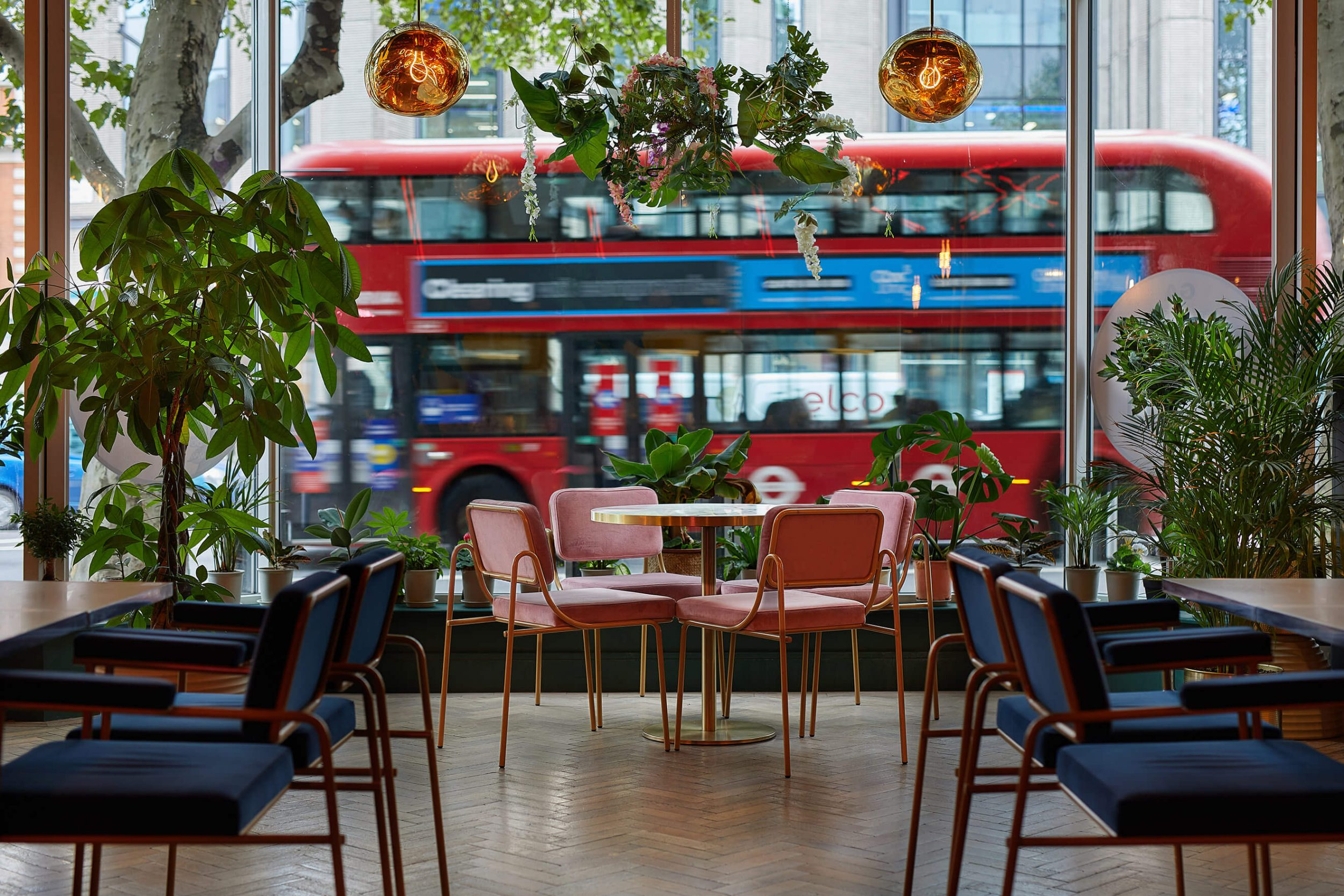 Large restaurant window view of red London bus